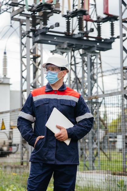 Um engenheiro de subestação elétrica inspeciona equipamentos modernos de alta tensão em uma máscara no momento da pondemia. energia. indústria. Foto Premium