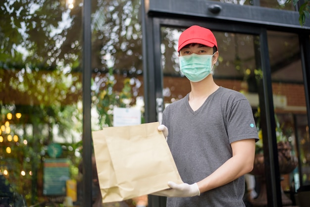 Um entregador asiático está usando máscara facial, segurando sacola de compras Foto Premium