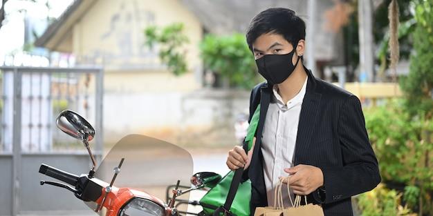 Um entregador está segurando uma sacola de papel ao lado de sua motocicleta. Foto Premium