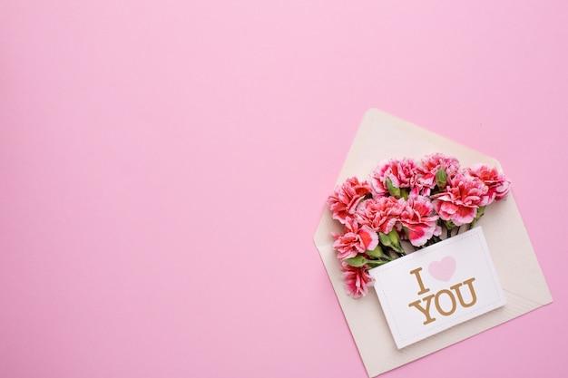 Um envelope com flores cor de rosa e um cartão eu te amo em rosa Foto Premium
