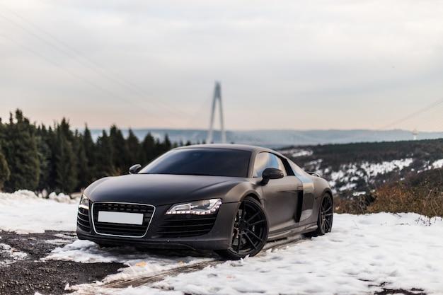 Um estacionamento preto luxuoso do cupê do esporte na estrada nevado na floresta. Foto gratuita