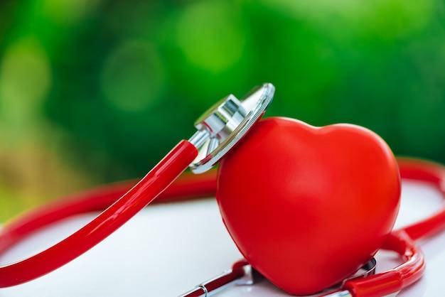 Um estetoscópio e um coração vermelho em fundos verdes de um bokeh. Foto Premium