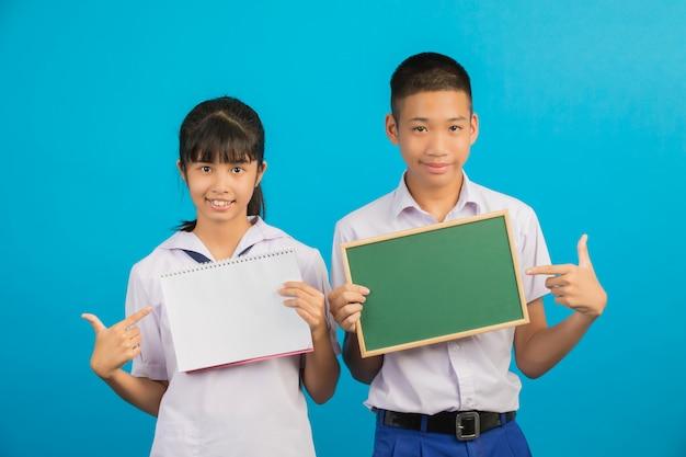 Um estudante asiático segurando um caderno andasian estudante do sexo masculino segurando uma placa verde em um azul. Foto gratuita
