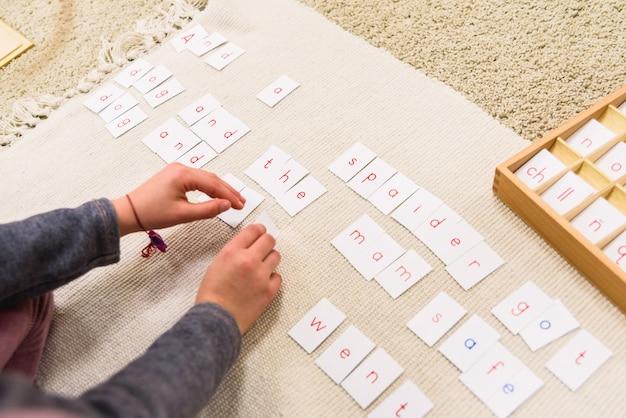 Um estudante de uma escola montessori usando cartões com letras Foto Premium