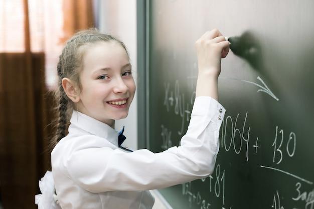 Um estudante fêmea da menina da escola primária escreve no quadro-negro. Foto Premium