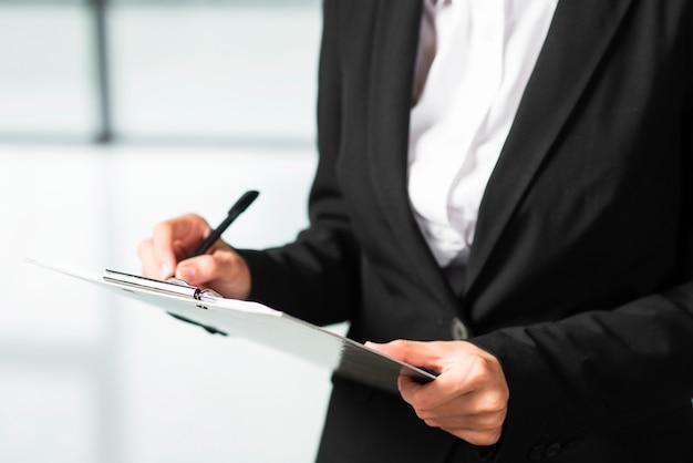 Um, executiva, escrita, ligado, área de transferência, com, caneta preta Foto gratuita