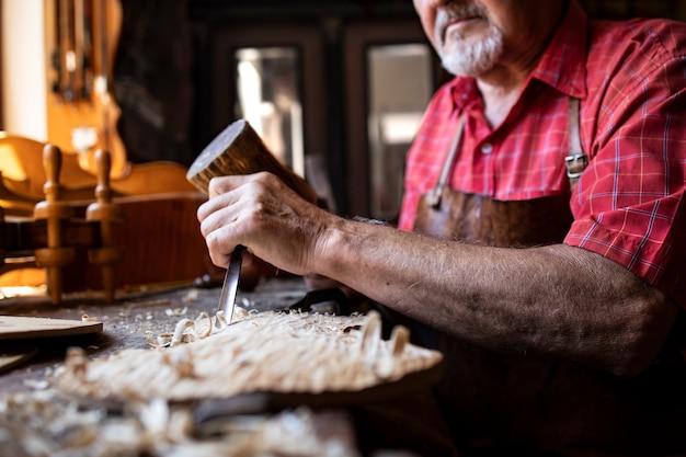 Um experiente carpinteiro experiente segurando uma faca e um martelo e esculpindo uma placa de madeira em sua oficina de marcenaria Foto gratuita