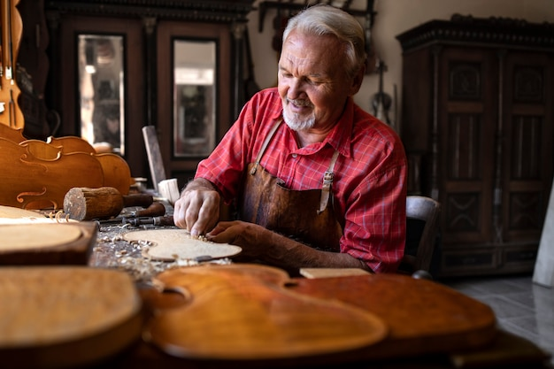 Um experiente carpinteiro sênior de cabelos grisalhos trabalhando em seu projeto em uma oficina de carpintaria Foto gratuita