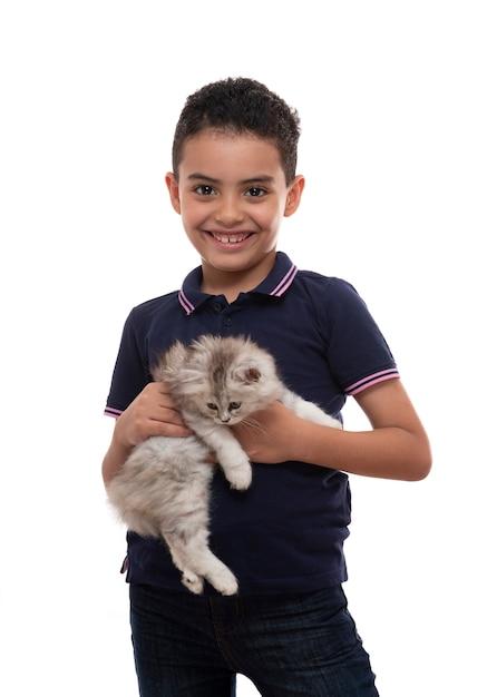 Um, feliz, menino jovem, sorrindo, com, peludo, gatinho, branco, fundo Foto Premium