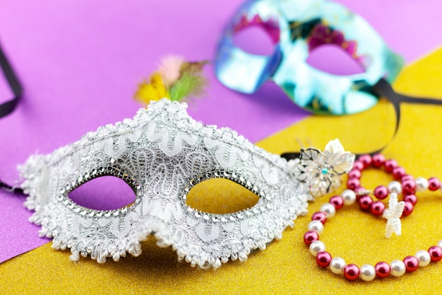 Um festivo, bonito branco mardi gras ou máscara de carnaval em fundo de papel colorido bonito Foto Premium