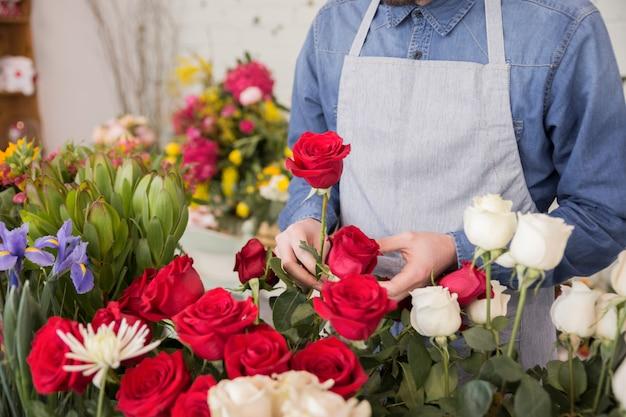 Um florista masculino organizando as rosas frescas na loja de florista Foto gratuita