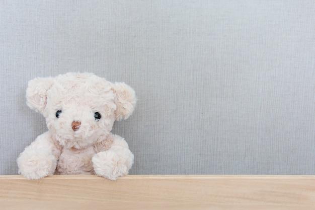 Um fofo urso de pelúcia está pegando na placa de madeira em cinza Foto Premium