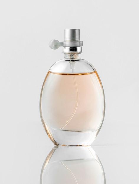 Um frasco de perfume de vista frontal transparente no chão branco Foto gratuita