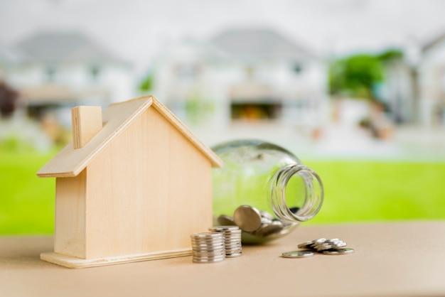 Um frasco de vidro aberto; moedas perto do modelo de casa de madeira na mesa ao ar livre Foto gratuita