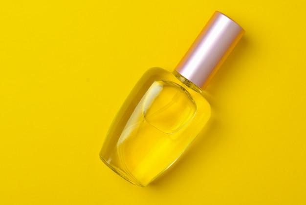 Um frasco de vidro de perfume feminino encontra-se sobre um fundo de papel amarelo. vista do topo. tendência do minimalismo. Foto Premium