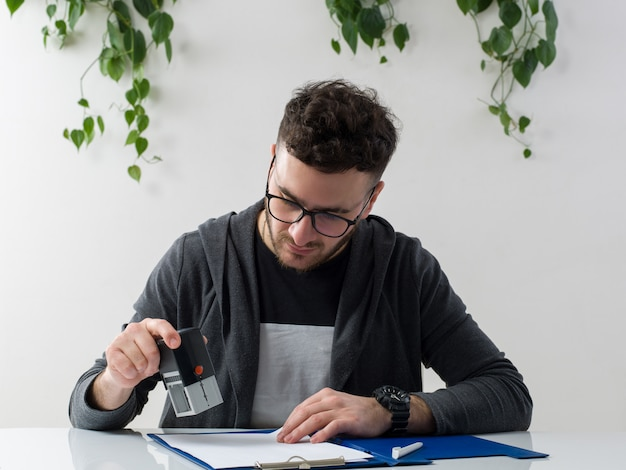 Um frotn vista jovem atraente em óculos de sol jaqueta cinza, trabalhando com documentos no chão branco Foto gratuita