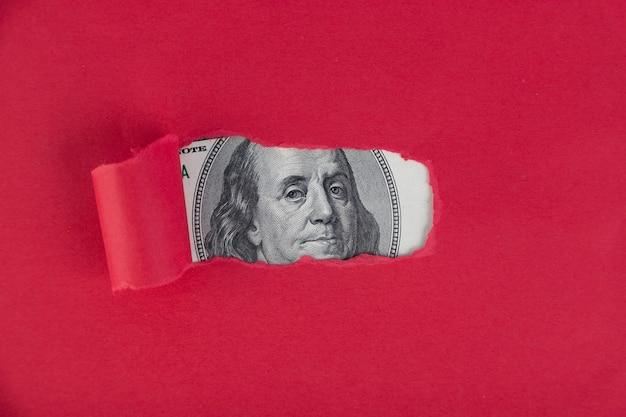 Um fundo vermelho, de onde aparece o retrato de uma nota de cinquenta dólares. conceito de empréstimo aprovado Foto Premium