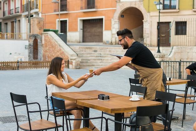 Um, garçom, é, servindo, um, café, para, um, mulher jovem, ligado, um, terraço bar Foto Premium