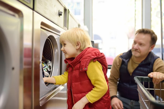 Um garotinho carrega roupas para a máquina de lavar roupa em lavandaria pública Foto Premium