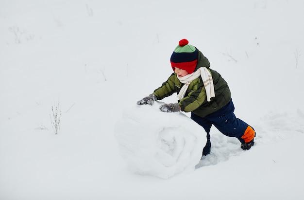 Um garotinho cria um boneco de neve Foto gratuita