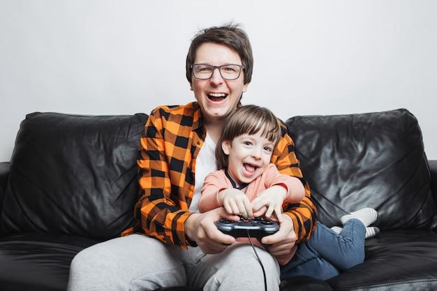 Um garotinho jogando videogame com o pai. Foto Premium