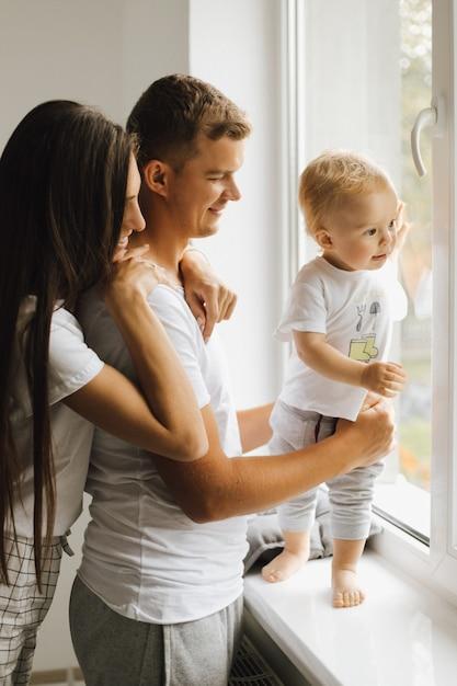 Um garotinho olha pela janela e seus pais o admiram Foto gratuita