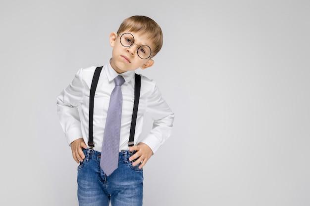 Um garoto charmoso de camisa branca, suspensórios, gravata e jeans claro fica em um fundo cinza. o garoto de óculos inclinou a cabeça para o lado Foto Premium