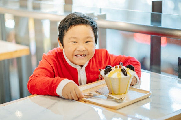 Um garoto fantasiado de papai noel e seu sorvete oreo. ele sorriu e ficou feliz. Foto Premium