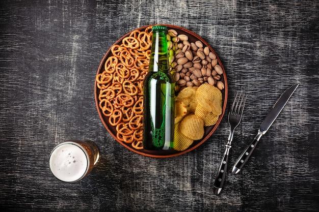 Um, garrafa cerveja, ligado, um, prato, com, salgado, ookies, pretzels, pistachio, nozes, e, lascas, ligado, um, pretas, riscado, junta giz Foto Premium