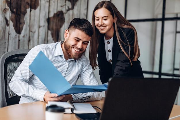 Um gerente sorridente e seu assistente trabalham no escritório Foto Premium