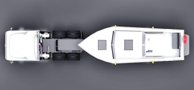 Um grande caminhão branco com um reboque para transportar um barco em uma superfície cinza Foto Premium
