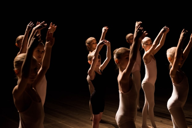 Um grande grupo de crianças ensaiando e dançando o balé Foto Premium