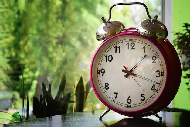 Um grande relógio despertador é rosa na mesa Foto Premium