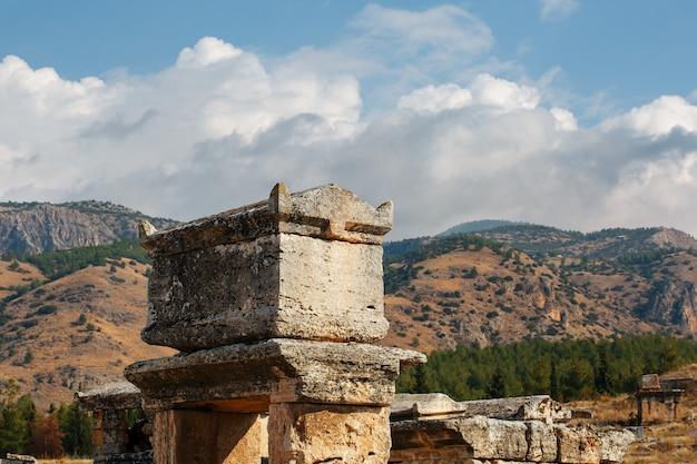 Um grande túmulo de pedra contra montanhas e céu em um grande cemitério em hierapolis. Foto Premium