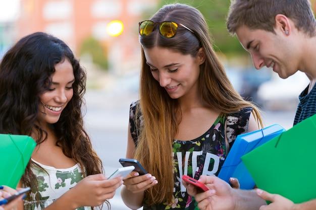 Um grupo de alunos se divertindo com smartphones após a aula. Foto gratuita