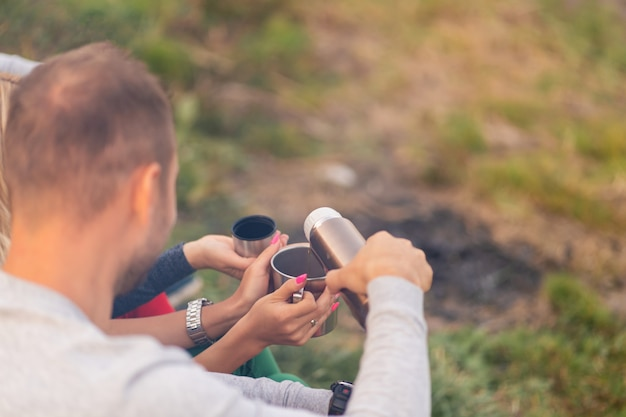 Um grupo de amigos está desfrutando de uma bebida quente de uma garrafa térmica, em uma noite fria ao lado de um incêndio na floresta. tempo divertido acampar com os amigos Foto Premium