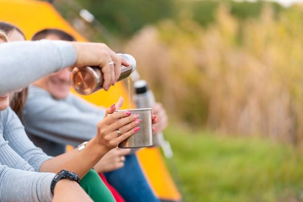 Um grupo de amigos está desfrutando de uma bebida quente de uma garrafa térmica, em uma noite fria ao lado de um incêndio na floresta Foto Premium