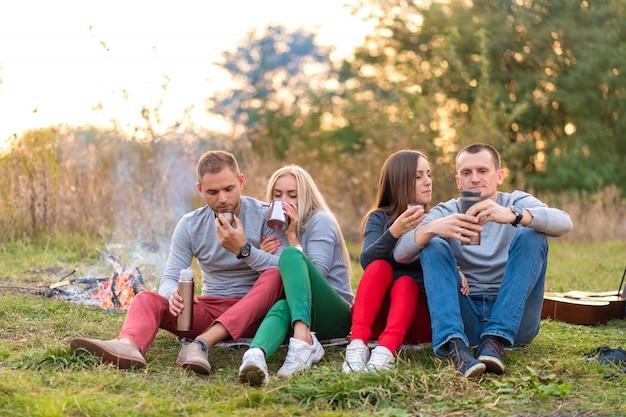 Um grupo de amigos está desfrutando de uma bebida quente de uma garrafa térmica, em uma noite fria por um incêndio na floresta. tempo divertido acampar com amigos Foto Premium