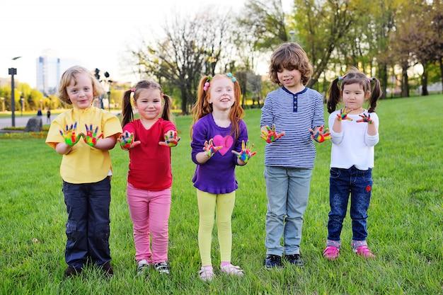 Um grupo de crianças pequenas com as mãos sujas no jogo da pintura da cor no parque. Foto Premium