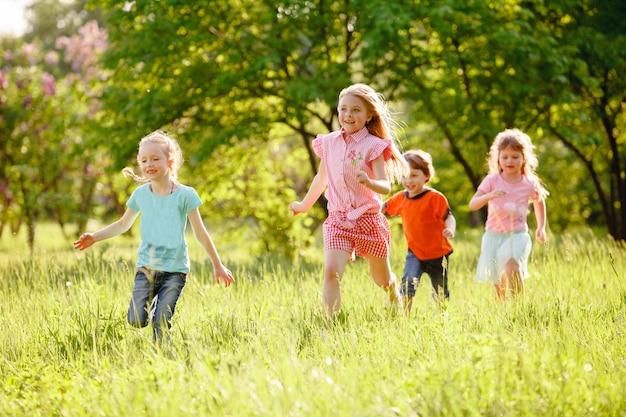Um grupo de crianças que jogam e que correm no parque em um gozon verde. Foto Premium