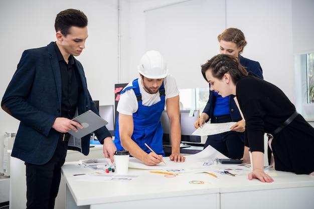 Um grupo de engenheiros profissionais, considerando cuidadosamente um projeto Foto Premium