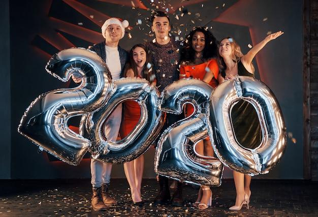 Um grupo de jovens multinacionais bonitas divertidas jogando confete em uma festa. feliz ano novo. Foto Premium
