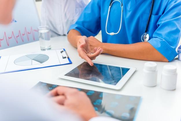 Um grupo de médicos está discutindo algo em um tablet. Foto Premium