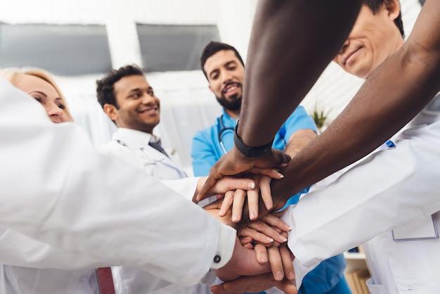 Um grupo de médicos está segurando as mãos uns dos outros. Foto Premium