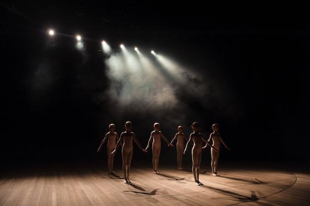 Um grupo de pequenos bailarinos ensaia no palco com luz e fumaça Foto Premium