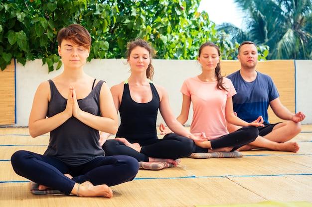 Um grupo de pessoas bonitas medita em uma aula de ioga no telhado Foto Premium