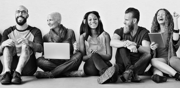 Um grupo de pessoas diversas está usando dispositivos digitais Foto gratuita