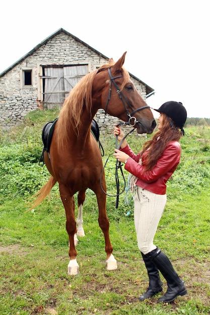 Um hipismo feminino com um cavalo marrom Foto gratuita