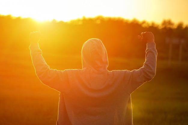 Um homem à luz do pôr do sol com as mãos para cima Foto Premium