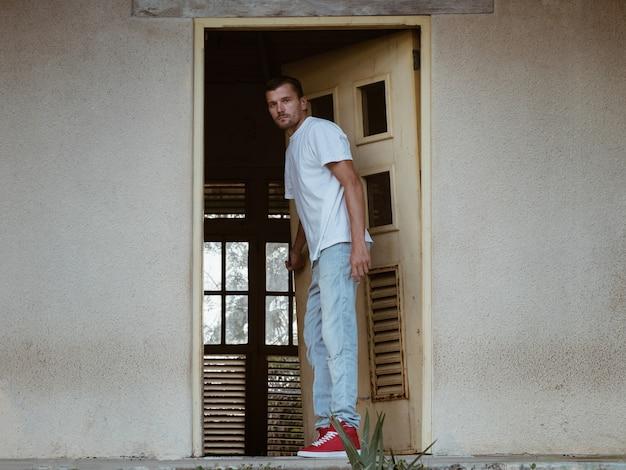 Um homem abre a porta de uma casa abandonada. Foto Premium